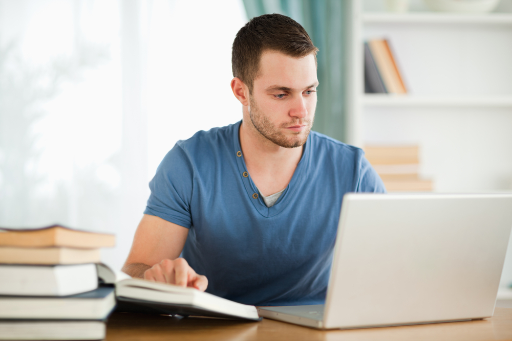 Male student researching material on the internet